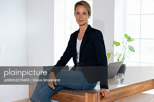 Confident businesswoman sitting on desk in home office - p300m2276433 by Steve Brookland