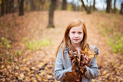 Young Red Hair Girl Playing Outside in Fall Leaves - p1166m2147059 by Cavan Images