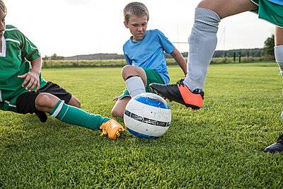 Young football players tackling on football ground - p300m1581201 von Fotoagentur WESTEND61