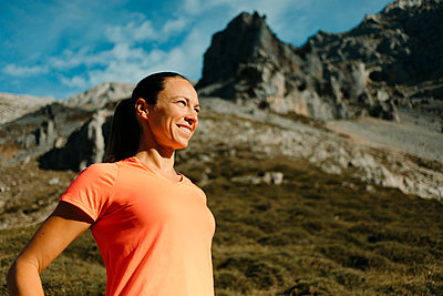 Female explorer smiling while standing against mountain at Cares Trail in Picos De Europe National Park, Asturias, Spain - p300m2250813 by David Molina Grande
