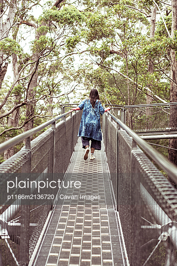 woman in big blue dress climbs along tree top walk in remote australia - p1166m2136720 by Cavan Images