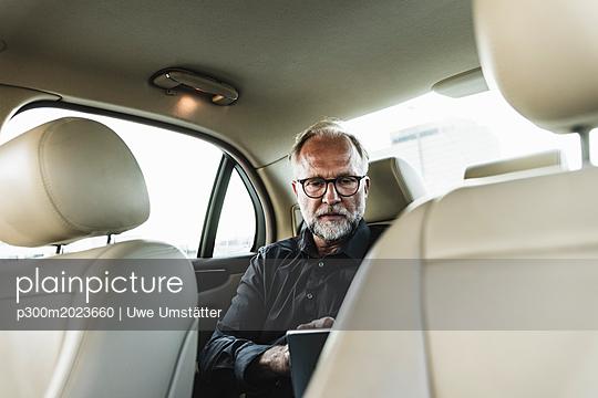 Mature businessman sitting on backseat in car, using digital tablet - p300m2023660 von Uwe Umstätter