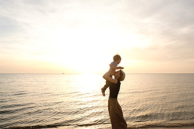 Young woman plays with her son near sea - p1363m2108791 by Valery Skurydin