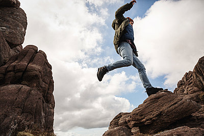 Hiker jumping across rocks - p1477m2038901 by rainandsalt