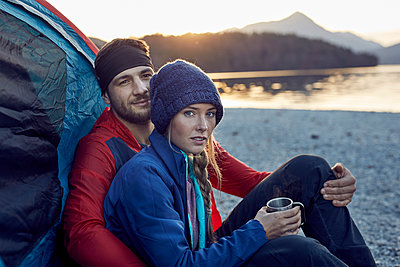 Young couple sitting at tent at lakeshore - p300m1562242 by Philipp Nemenz