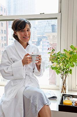 A woman wearing a bathrobe sitting on a window sill and holding a mug - p30119645f by Emiliano Granado