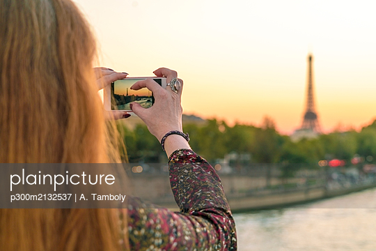 France, Paris, Woman taking photo with mobile phone - p300m2132537 by A. Tamboly