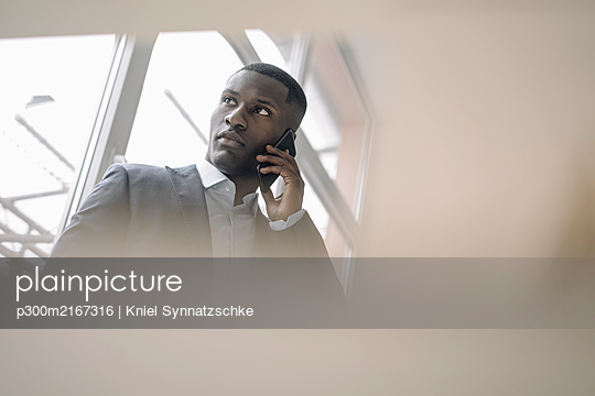 Portrait of young businessman in front of window on the phone - p300m2167316 by Kniel Synnatzschke