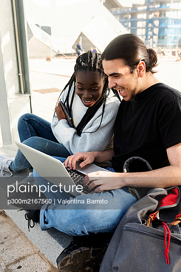Happy young couple using laptop at tram stop - p300m2167560 by Valentina Barreto