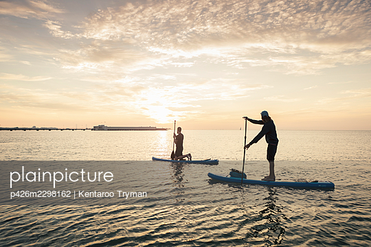 Man learning to paddleboard from male instructor in sea during sunset - p426m2298162 by Kentaroo Tryman
