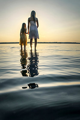 Mother and Daughter facing sunset in river - p1019m1133605 by Stephen Carroll