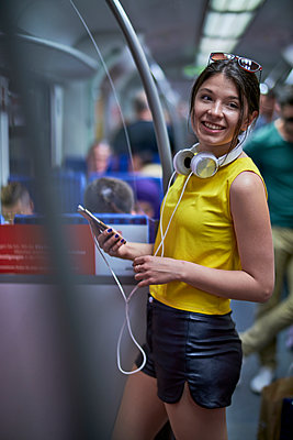 Portrait of smiling young woman with cell phone and headphones in underground train - p300m1587667 by Benjamin Egerland