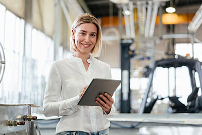 Portrait of smiling young woman using tablet in a factory - p300m2188301 by Daniel Ingold