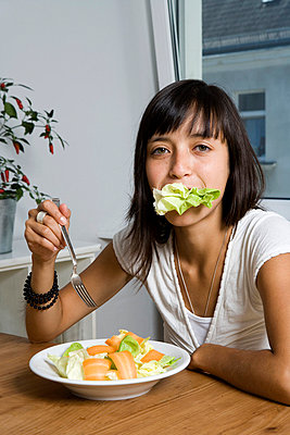 A woman sitting at a table and eating a salad - p3016804f by Halfdark