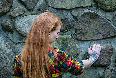 Rothaarige Frau an einer Mauer - p427m1537848 von R. Mohr