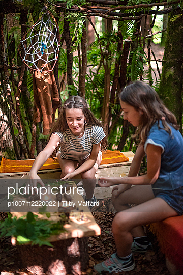 Two girls doing handicrafts together in a hut in the forest - p1007m2220022 by Tilby Vattard