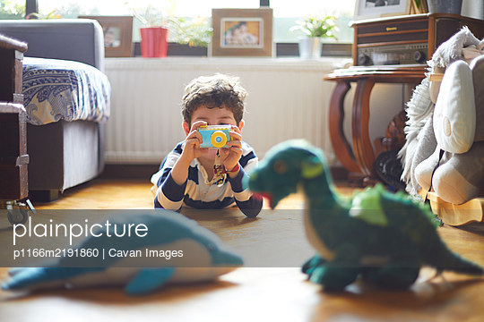A boy takes photos of his toys with his camera - p1166m2191860 by Cavan Images