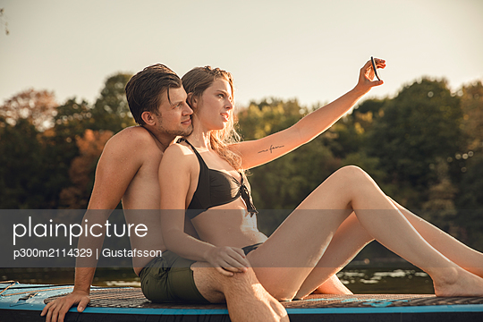 Happy couple sitting on paddleboard on a lake, taking smartphone selfies - p300m2114329 von Gustafsson