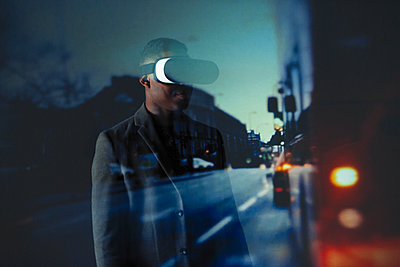 Double exposure businessman with virtual reality simulator glasses against city street  - p1023m2135728 by Paul Bradbury