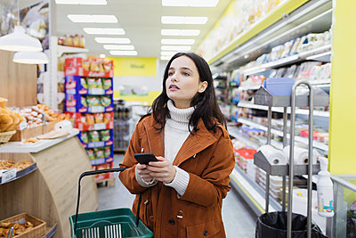 Woman with smart phone shopping in supermarket - p1023m2187656 by Sam Edwards