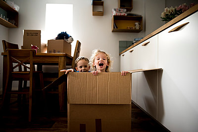 Portrait of cheerful siblings sitting in cardboard box at home - p1166m1414746 by Cavan Images