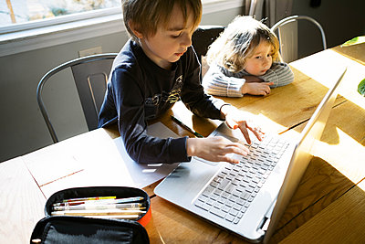 kids in morning light sitting at table doing remote school - p1166m2232737 by Cavan Images
