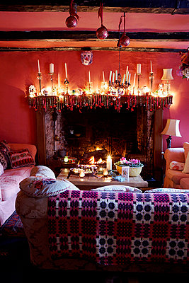 Lit candles on mantlepiece in living room of 16th Century Welsh farmhouse  - p349m789962 by Brent Darby