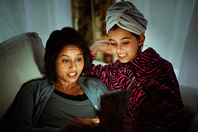 Mixed race mother and daughter using digital tablet at night - p555m1421082 by Donald Iain Smith