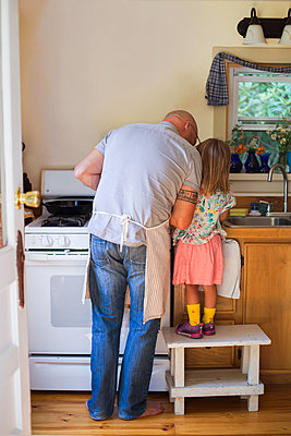 Rear view of girl on stool watching father preparing food in kitchen - p924m1557836 by Kinzie Riehm