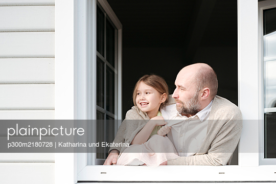 Mature man with smiling daughter looking out of window of their house - p300m2180728 by Katharina und Ekaterina