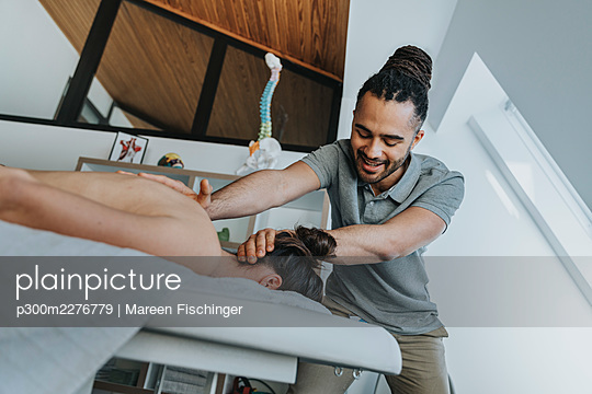 Smiling male physiotherapist giving massage to female patient in medical practice - p300m2276779 by Mareen Fischinger