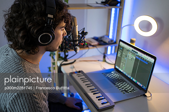 Young music composer with headphones and piano using laptop at home - p300m2281745 by Francesco Buttitta