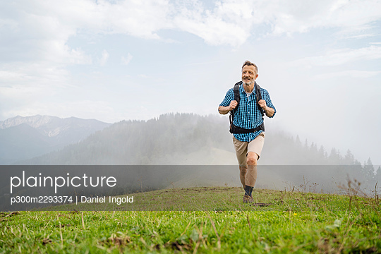 Mature male hiker walking on mountain - p300m2293374 by Daniel Ingold