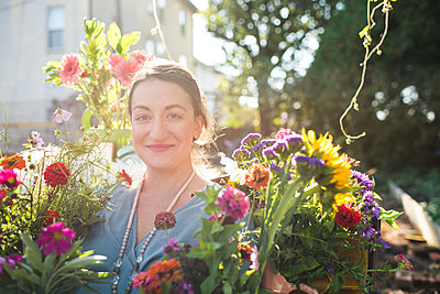 happy woman in a flower garden in the sunshine - p1166m2136964 by Cavan Images