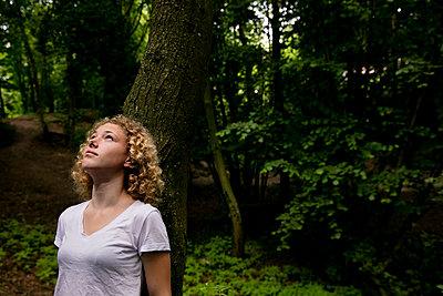Mädchen lehnt an einem Baum im Wald - p1212m1152921 von harry + lidy