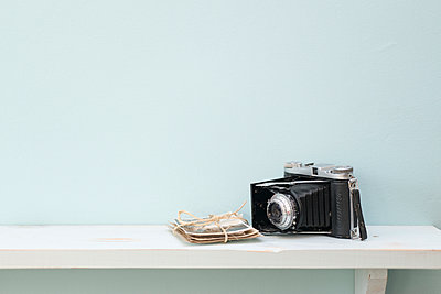 Vintage folding rangefinder camera with a bundle of black and white photographic prints. - p1433m2013821 by Wolf Kettler