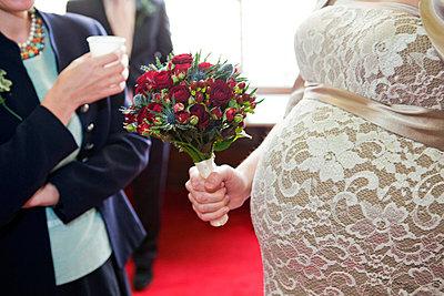 Pregnant bride holding flower bouquet - p3882834 by Bill Davies