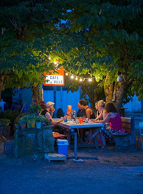 Three generation family at cafe table at night, France - p429m1103135 by Planet Pictures