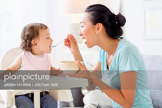 Mother feeding baby daughter in high chair - p555m1410594 by JGI/Tom Grill