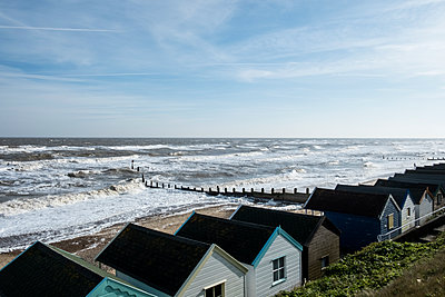 Seascape over a row of wooden beach huts, with waves rolling onto beach near groyne.  - p1100m1575773 by Mint Images