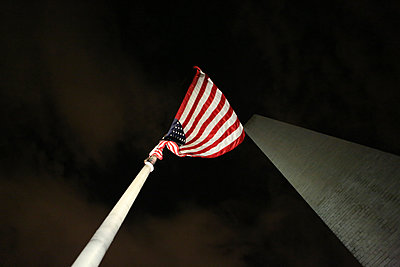Low angle view of American flag by Washington Monument against sky - p1166m1210073 by Cavan Images