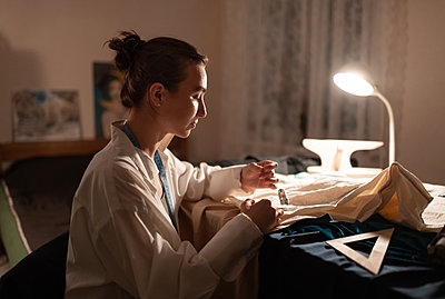 Designer sewing in lamplight working lately - p1166m2218581 by Cavan Images