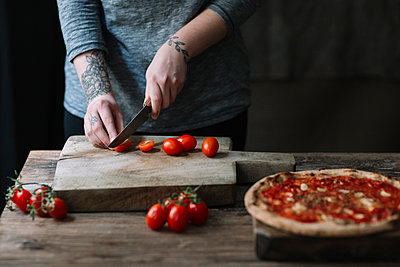 Young woman preparing pizza, cutting tomatoes on chopping board - p300m2083166 von Alberto Bogo
