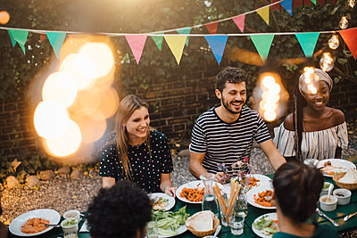 Happy multi-ethnic friends enjoying dinner at table during garden party - p426m2046166 by Maskot
