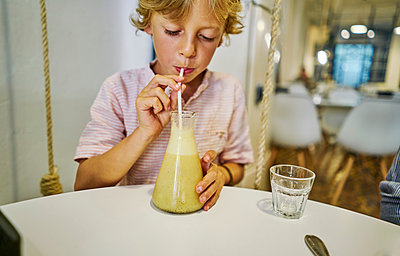 Boy drinking juice through straw - p429m1519593 by Stephen Lux