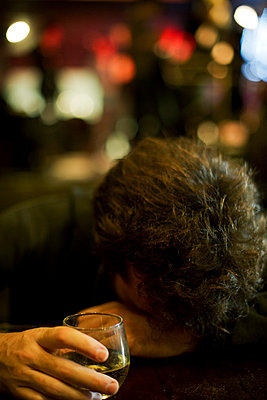 Man at bar with glass of whisky resting head on arms - p675m922743 by Frederic Cirou