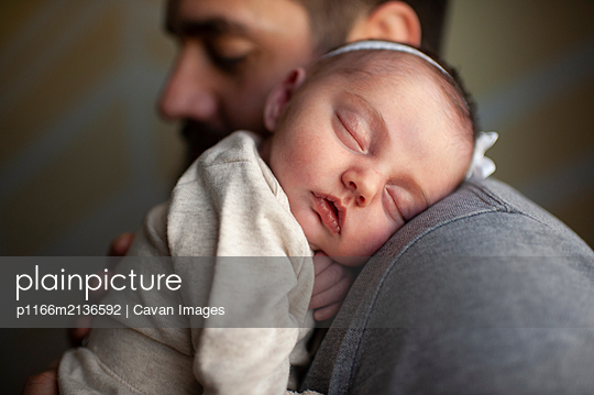 Close up of newborn baby's face sleeping on father's shoulder at home - p1166m2136592 by Cavan Images