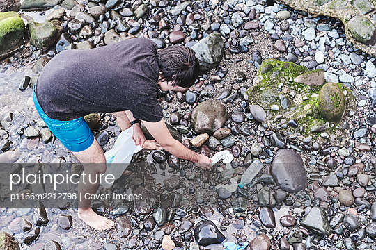 Anonymous Volunteer Cleaning Beach From Plastic - p1166m2212798 by Cavan Images