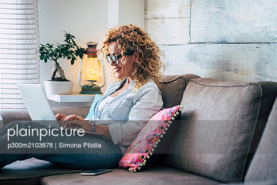 Smiling woman using laptop on couch at home - p300m2103878 von Simona Pilolla