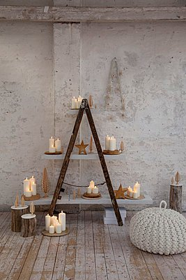 Lit candles on home-made shelving with white shelves in rustic atmosphere - p1183m996981 by Grossmann.Schuerle
